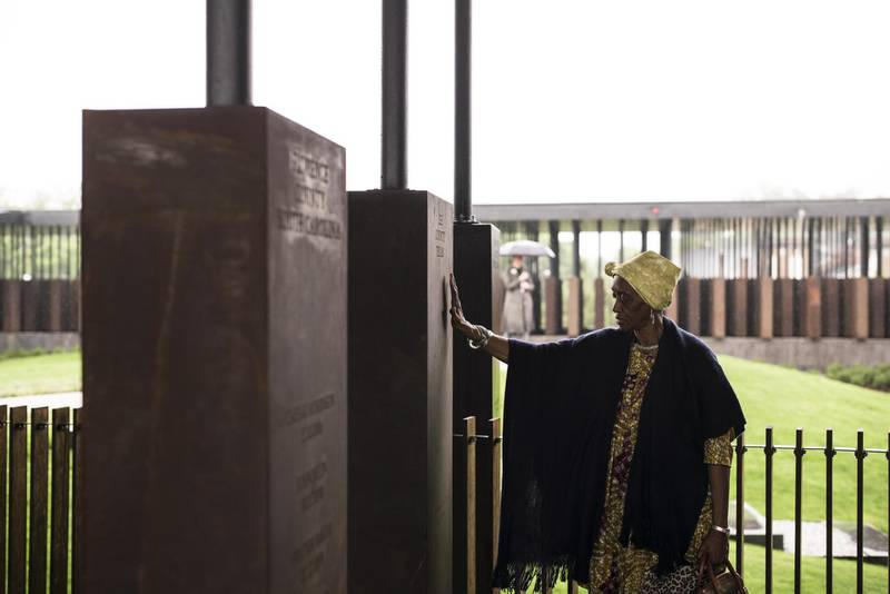 """MONTGOMERY, AL - APRIL 26: Wretha Hudson, 73, discovers a marker commemorating lynchings in Lee County, Texas while visiting the National Memorial For Peace And Justice on April 26, 2018 in Montgomery, Alabama. Hudson, whose father's family came to Alabama from Lee County decades earlier, said the experience was overwhelming. """"It's a combination of pride and strength, for my people. In our culture, rain is a sign of acceptance from our ancestors. So the rain is a sign of their acceptance for this day."""" The memorial is dedicated to the legacy of enslaved black people and those terrorized by lynching and Jim Crow segregation in America. Conceived by the Equal Justice Initiative, the physical environment is intended to foster reflection on America's history of racial inequality.   Bob Miller/Getty Images/AFP"""