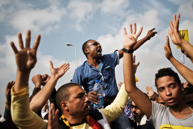 """Egyptian supporters of the Muslim Brotherhood or ousted president Mohammed Morsi shout slogans in his support during a protest outside the Police Academy where Morsi's trial takes place on November 4, 2013 in Cairo, Egypt. Morsi appeared in court on the first day of his trial, rejecting its legitimacy and demanding """"coup"""" leaders be prosecuted, as thousands of his supporters rallied. -- shows a sign with the four fingers, the symbol known as """"Rabaa"""", which means four in Arabic, remembering those killed in the crackdown on the Rabaa al-Adawiya protest camp in Cairo earlier in the yearAFP PHOTO/GIANLUIGI GUERCIA *** Local Caption ***  fo24no-Egypt-DueProc-p11.jpg"""