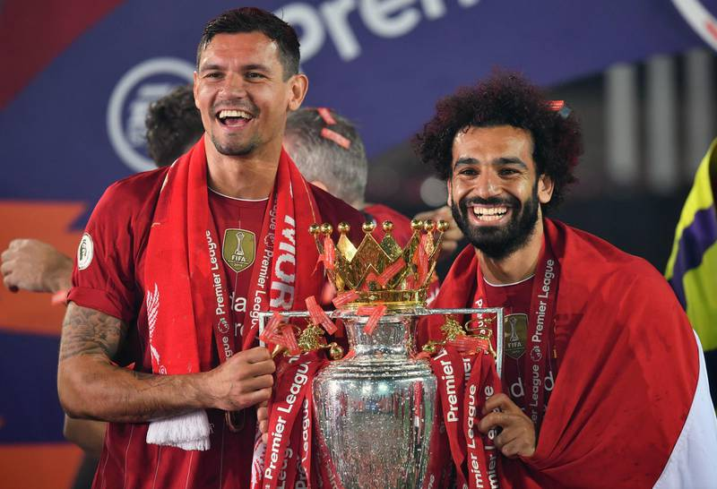 """Liverpool's Dejan Lovren and Mohamed Salah lift the Premier League Trophy at Anfield. PA Photo. Picture date: Wednesday July 22, 2020. See PA story SOCCER Liverpool. Photo credit should read: Paul Ellis/NMC Pool/PA Wire. RESTRICTIONS: EDITORIAL USE ONLY No use with unauthorised audio, video, data, fixture lists, club/league logos or """"live"""" services. Online in-match use limited to 120 images, no video emulation. No use in betting, games or single club/league/player publications."""