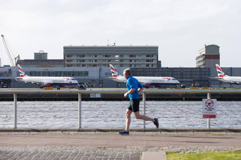 LONDON, ENGLAND - MARCH 29: A jogger passes grounded aeroplanes at London City Airport on March 29, 2020 in London, England. The field hospital will initially contain 500 beds with ventilators and oxygen and will have the capacity to eventually hold up to 4,000 COVID-19 patients. (Photo by Hollie Adams/Getty Images)