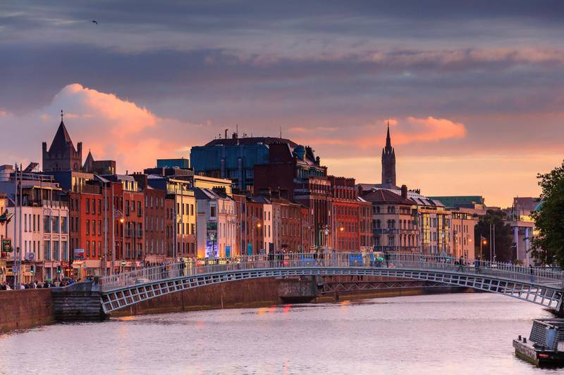 People walking on the Half Penny Bridge at sunset, Dublin Ireland