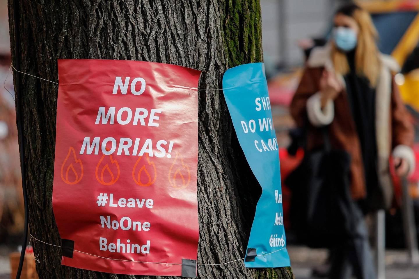 """Posters calling for """"No more Morias"""" referring to the Moria refugee camp on the Greek island of Lesbos which burned down, are hung on a tree on February 18, 2021 in Berlin's Kreuzberg district.  Lesbos' squalid Moria migrant camp was ravaged by two fires in September. It has since been replaced by a hastily-erected temporary encampment in an area prone to flooding and strong winds. Aid groups have denounced the poor conditions and the lack of infrastructure on the site, while media outlets have complained that they are banned from entering.  / AFP / David GANNON"""