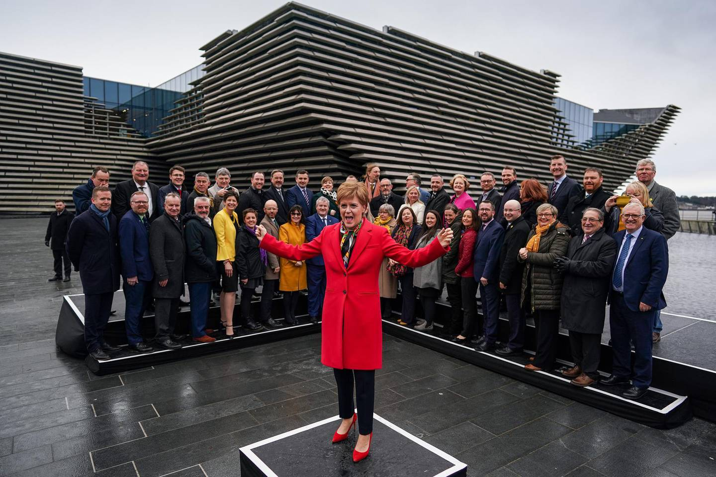 """DUNDEE, SCOTLAND - DECEMBER 14: First Minister, Nicola Sturgeon, joins the SNPs newly elected MPs for a group photo outside the V&A Museum on December 14, 2019 in Glasgow, Scotland.The Scottish National Party (SNP) won 48 out of a possible 59 Westminster seats in the UK general election. Leader of the SNP, Nicola Sturgeon said the win is a """"mandate for Indyref2"""" to decide if Scotland remains part of the United Kingdom. (Photo by Jeff J Mitchell/Getty Images)"""