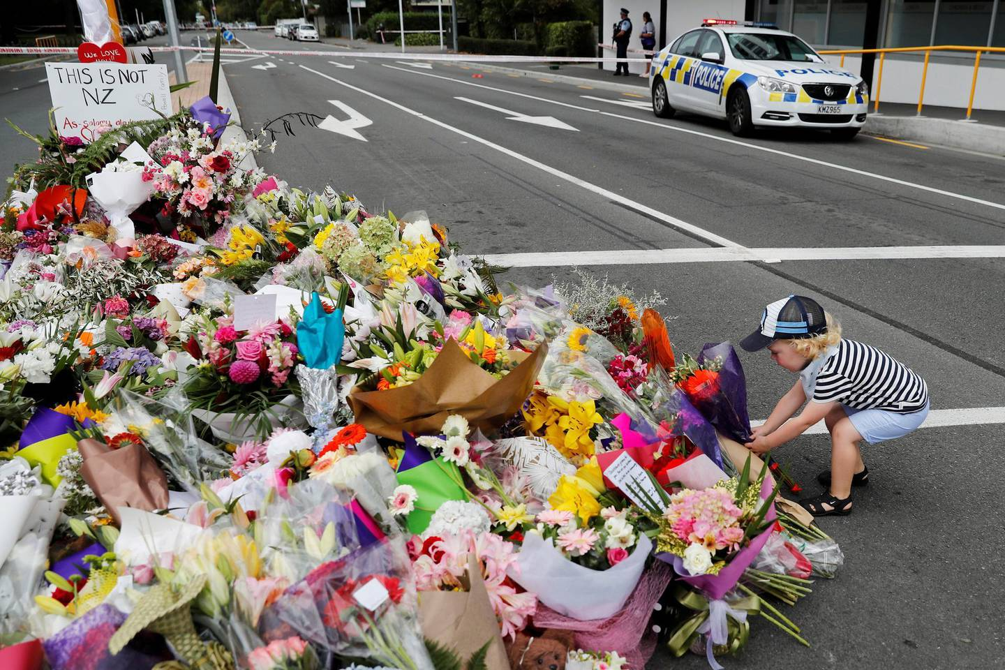 A boy places flowers at a memorial as a tribute to victims of the mosque attacks, near a police line outside Masjid Al Noor in Christchurch, New Zealand, March 16, 2019. REUTERS/Jorge Silva     TPX IMAGES OF THE DAY