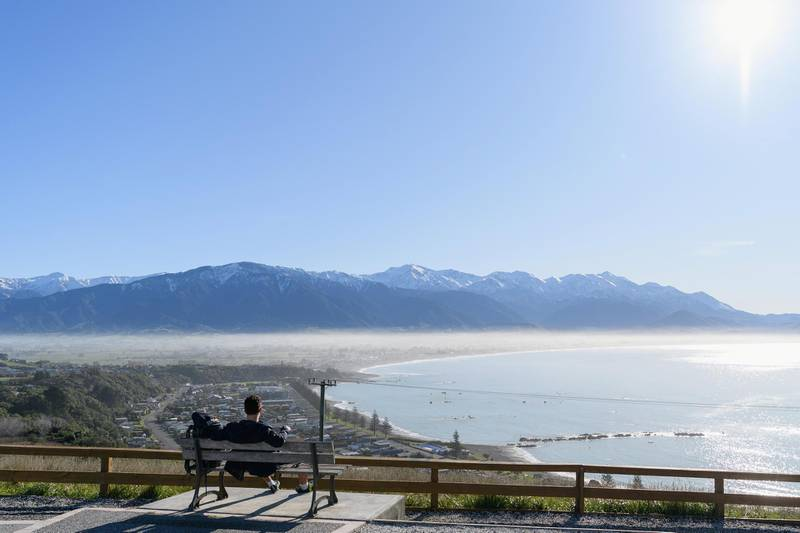 KAIKOURA, NEW ZEALAND - JUNE 10: A backpacker enjoys the view of Kaikoura and the Kaikoura Ranges on June 10, 2020 in Kaikoura, New Zealand. New Zealanders are adjusting as life begins to return to normal following the lifting of COVID-19 restrictions on Tuesday 9 June. The move to Alert Level 1 and lifting of almost all restrictions comes after the government confirmed zero active cases in New Zealand. While the easing of restrictions will see life mostly return to normal across the country, strict border measures will remain with mandatory 14-day isolation and quarantine for any overseas arrivals. The coastal tourist town of Kaikoura relies heavily on international tourism, with local businesses deeply impacted by the closure of borders in response to the COVID-19 pandemic. Although domestic tourists are now able to return, the Kaikoura community is hoping a Trans-Tasman travel bubble allowing tourists from Australia to come to New Zealand will soon be established. (Photo by Kai Schwoerer/Getty Images)