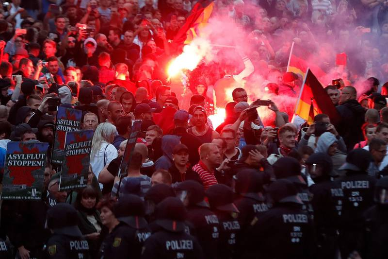 """TOPSHOT - Right wing demonstrators light flares on August 27, 2018 in Chemnitz, eastern Germany, following the death of a 35-year-old German national who died in hospital after a """"dispute between several people of different nationalities"""", according to the police. - The far-right street movement PEGIDA called for a second day of protests in Chemnitz in ex-communist eastern Germany after the alleged fatal stabbing of a German man by a foreigner. (Photo by Odd ANDERSEN / AFP)"""
