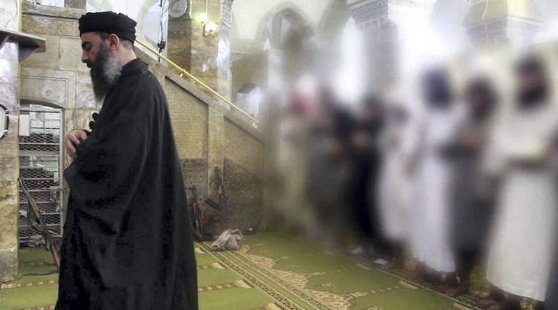 """An image grab taken from a propaganda video released on July 5, 2014 by al-Furqan Media allegedly shows the leader of the Islamic State (IS) jihadist group, Abu Bakr al-Baghdadi, aka Caliph Ibrahim, leading prayers next to machine guns with Muslim worshippers behind him, whose picture was blurred from the source, at a mosque in the militant-held northern Iraqi city of Mosul. Baghdadi, who on June 29 proclaimed a """"caliphate"""" straddling Syria and Iraq, purportedly ordered all Muslims to obey him in the video released on social media.    AFP PHOTO / HO / AL-FURQAN MEDIA  == RESTRICTED TO EDITORIAL USE - MANDATORY CREDIT """"AFP PHOTO / HO / AL-FURQAN MEDIA """" - NO MARKETING NO ADVERTISING CAMPAIGNS - DISTRIBUTED AS A SERVICE TO CLIENTS FROM ALTERNATIVE SOURCES, AFP IS NOT RESPONSIBLE FOR ANY DIGITAL ALTERATIONS TO THE PICTURE'S EDITORIAL CONTENT, DATE AND LOCATION WHICH CANNOT BE INDEPENDENTLY VERIFIED == (Photo by - / AL-FURQAN MEDIA / AFP)"""
