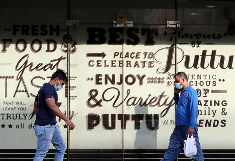 Dubai, United Arab Emirates - Reporter: N/A. Street Photography. People walk passed a restaurant in Al Karama. Sunday, April 18th, 2021. Dubai. Chris Whiteoak / The National