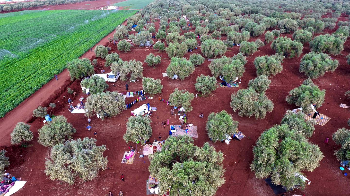 An aerial view shows displaced Syrians gathering in a field near a camp for displaced people in the village of Atme, in the jihadist-held northern Idlib province on May 8, 2019. - In the olive grove in Atme, dozens of families have spent the night on thin mattresses or blankets layed out over rugs on the red earth. At the base of the trees they have chosen for shelter, they have stored the bare minimum for a life outdoors: bedding, a water cooler, a saucepan, or a cooking gas canister. They have hung up sheets between the trees for a little privacy, and one family has even brought a solar panel. (Photo by Aaref WATAD / AFP)