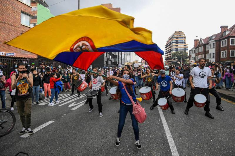 TOPSHOT - A woman waves a Colombian national flag during a protest against a tax reform proposed by Colombian President Ivan Duque's government in Bogota, on May 4, 2021.  The international community on Tuesday decried what the UN described as an 'excessive use of force' by security officers in Colombia after official data showed 19 people were killed and 846 injured during days of anti-government protests.  / AFP / Juan BARRETO