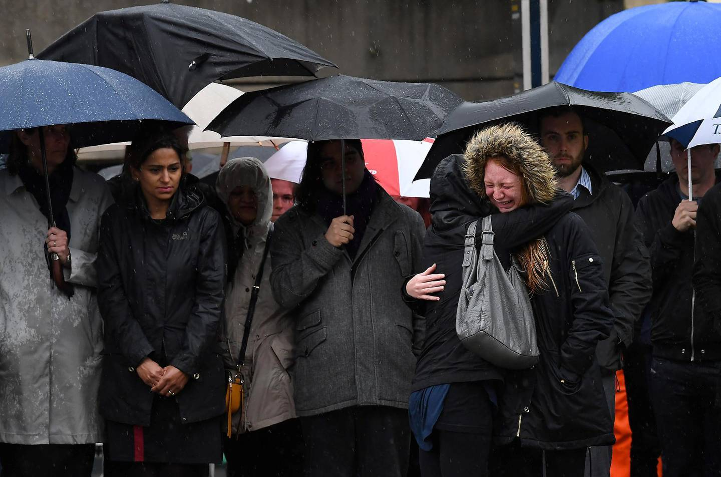 A woman reacts as people observe a minutes' silence at south-side of London Bridge in London on June 6, 2017, in memory of the victims of the June 3 terror attacks. Police on Monday identified two of the three London attackers as Khuram Butt and Rachid Redouane, after Britain's third terror assault in less than three months, as Prime Minister Theresa May came under mounting pressure over security just days ahead of elections. / AFP PHOTO / Justin TALLIS