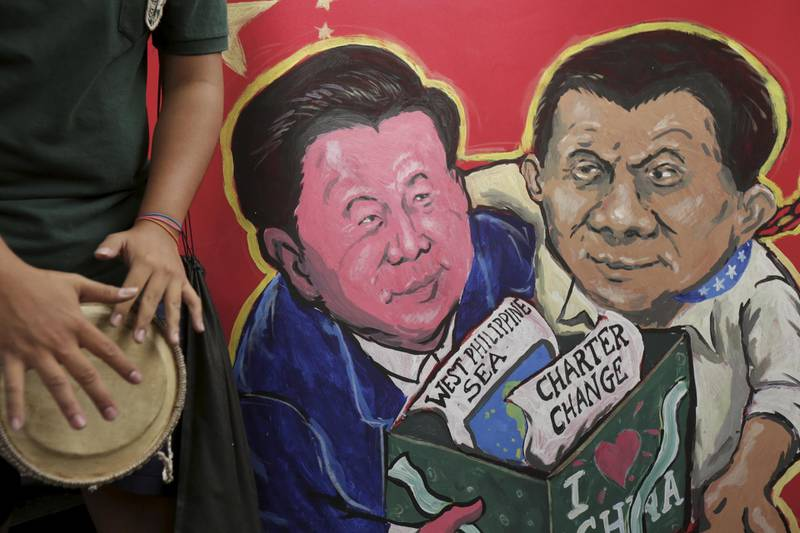 epa07178645 A placard with painting depicting Chinese President Xi Jinping and Philippine president Rodrigo Duterte during a protest near the Chinese Embassy upon the arrival of Chinese President Xi Jinping in Manila, Philippines, 20 November 2018. President Xi Jinping is in Manila for a two day state visit, during which he will attend a series of bilateral meetings and signing agreement ceremonies.  EPA/STR