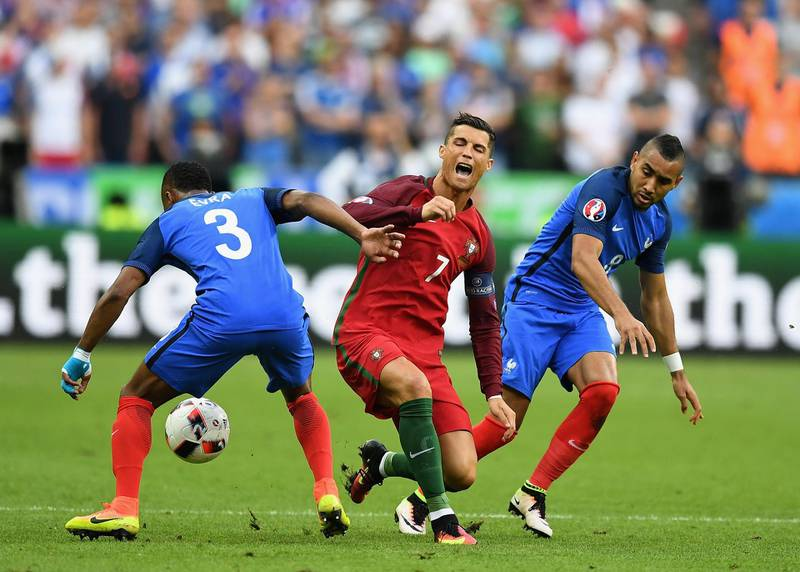 PARIS, FRANCE - JULY 10:  Cristiano Ronaldo (C) of Portugal is challenged by Patrice Evra (L) and Dimitri Payet (R) of France during the UEFA EURO 2016 Final match between Portugal and France at Stade de France on July 10, 2016 in Paris, France.  (Photo by Laurence Griffiths/Getty Images)