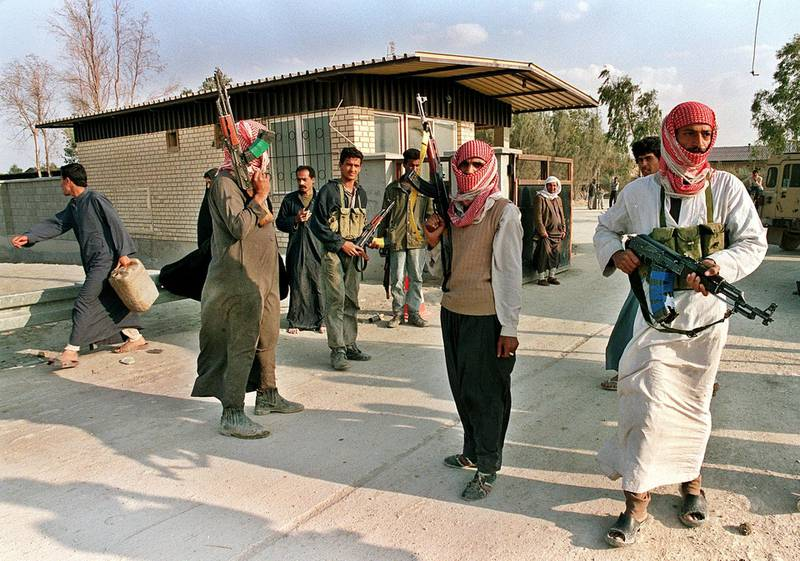 (FILES) Picture dated 27 March 1991 shows armed Iraqi rebels at their camp in the outskirts of the southern Iraqi city of Nassiriya. Iraqi security forces smashed Shiite protests killing at least 15 people, arresting almost 250 in Baghdad alone and restricting unrest 21 February to Nassiriya, the opposition said. The Supreme Council for Islamic Revolution in Iraq said the Iraqi army shelled areas of Nassiriya over which it lost control to rioters who attacked government buildings. (Photo by MANOOCHER DEGHATI / AFP FILES / AFP)
