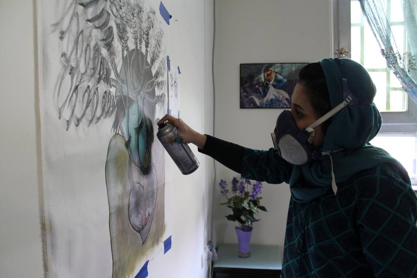 Shamsia Hassani working in her living room. When too dangerous to go on streets of Kabul Hassani works at home. Picture by Sarvy Geranpayeh