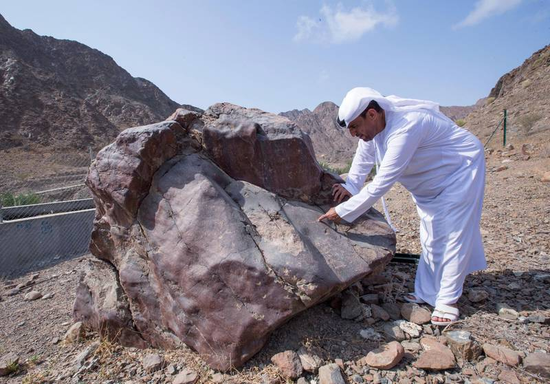Sharjah, United Arab Emirates-  Abdullah Khilfan Al Naqbi showing early writings in a hill written on a big rock at Al Nahwa Village in Sharjah.  Leslie Pableo for The National for Ruba Haza