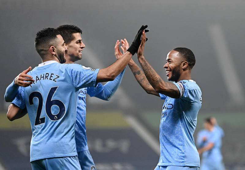 WEST BROMWICH, ENGLAND - JANUARY 26: Raheem Sterling of Manchester City celebrates after scoring his sides fifth goal with team-mates Riyad Mahrez and Joao Cancelo during the Premier League match between West Bromwich Albion and Manchester City at The Hawthorns on January 26, 2021 in West Bromwich, England. Sporting stadiums around the UK remain under strict restrictions due to the Coronavirus Pandemic as Government social distancing laws prohibit fans inside venues resulting in games being played behind closed doors. (Photo by Laurence Griffiths/Getty Images)