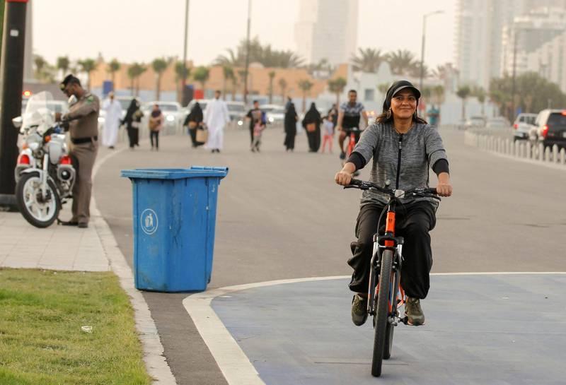 Eman Joharjy, a fashion designer in one of her own creations, cycles along Jaddah's Corniche, Saudi Arabia June 24, 2018. Picture taken June 24, 2018. REUTERS/Zohra Bensemra