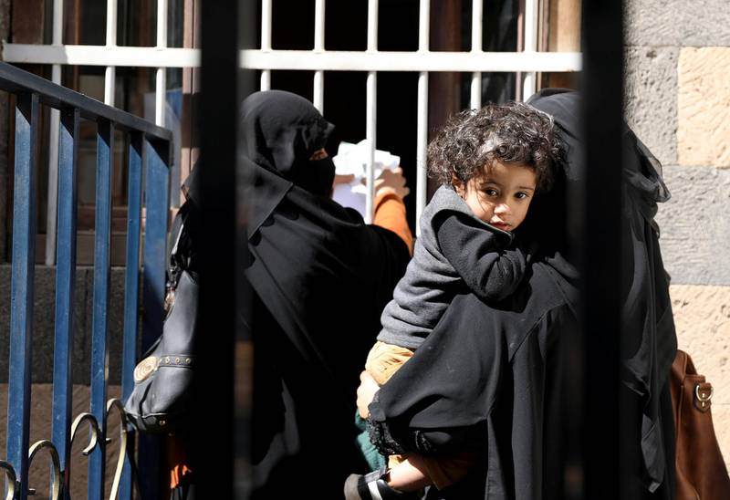 Women and a boy wait for foodstuff assistance vouchers at an aid distribution center in Sanaa, Yemen January 25, 2021. Picture taken January 25, 2021. REUTERS/Khaled Abdullah
