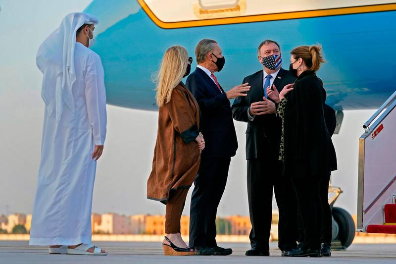 US Secretary of State Mike Pompeo (2nd-R) and his wife Susan (R) speak with US Ambassador to the United Arab Emirates John Rakolta and his wife Terry after stepping off a plane at al-Bateen Executive Airport in Abu Dhabi on November 20, 2020.  / AFP / POOL / Patrick Semansky