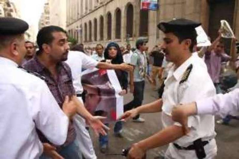 Egyptian policemen confront a demonstrator during a rally in support of slain 28-year-old Khaled Said in Cairo, Egypt Sunday, June 20, 2010, after the police allegedly  beat Khaled, a young businessman, to death on an Alexandria street after he posted a video on the Internet of officers sharing the spoils from a drug bust among themselves, his family said. (AP Photo/Ahmed Gomaa)          *** Local Caption ***  AMR103_Mideast_Egypt_Police_Beating.jpg