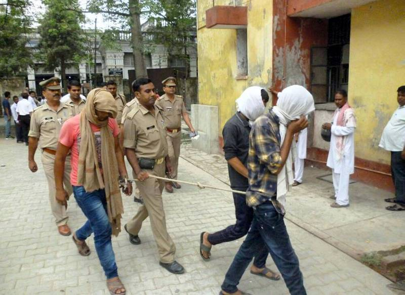 Indian police escort three suspects arrested in connection with a video posted on social media showing a sexual assualt at the district court in Rampur in May 29, 2017.  Indian police arrested three men who put up video on social media showing them assaulting two women in broad daylight as a dozen others watched, ignoring screams for help. Blurry video aired on Indian broadcasters showed the men groping and pushing the women in Uttar Pradesh state as onlookers laughed and filmed the assault. / AFP PHOTO / STR