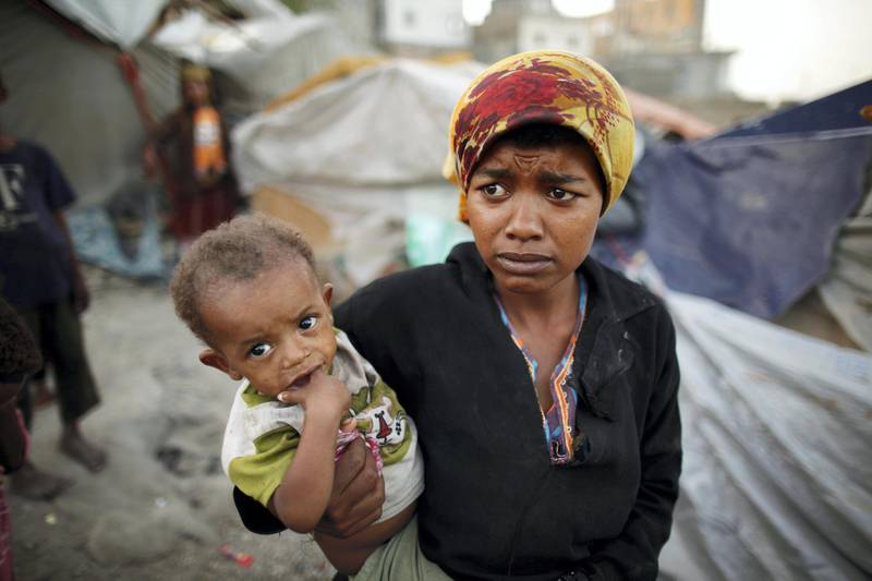 A woman from the Akhdam community holds her son in a slum area in Yemen's southwestern city of Taiz October 11, 2012. Yemeni Akhdam, or servants, are similar to hereditary castes, but are distinguished by their African features and the menial jobs they perform. Widespread prejudice places the Akhdam at the bottom of Yemen's social ladder. Asked about the origins of the Akhdam, Yemenis say they are descendants of Ethiopians who crossed the Red Sea to conquer Yemen before the arrival of Islam some 1,400 years ago - making them outsiders in their own country. Most live in slum areas in the outskirts of the capital Sanaa and other main cities. They reside in small huts haphazardly built of wood and cloth, without basic services such as running water, electricity and sewage networks. Picture taken October 11, 2012. REUTERS/Khaled Abdullah (YEMEN - Tags: SOCIETY POVERTY)  ATTENTION EDITORS: PICTURE 12 OF 20 FOR PACKAGE 'YEMEN'S UNDERCLASS' SEARCH 'AKHDAM' FOR ALL IMAGES