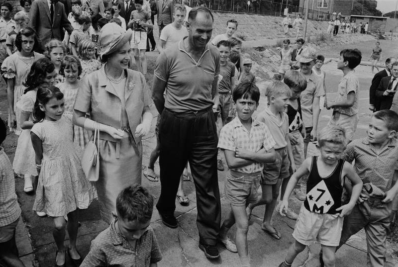Queen Elizabeth II pictured with a guide surrounded by school children at a children's playground in Sydney during a Commonwealth visit to Australia in February 1963. (Photo by Daily Express/Hulton Archive/Getty Images)