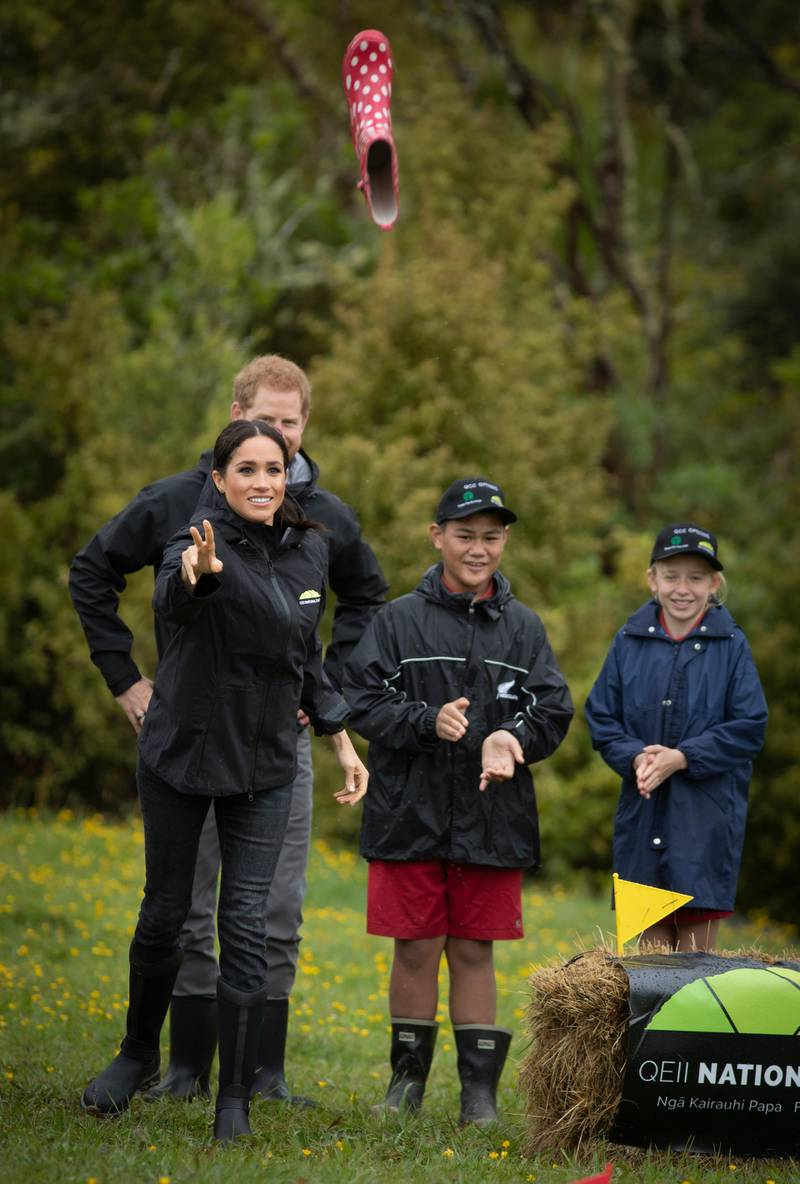 AUCKLAND, NEW ZEALAND - OCTOBER 30: Prince Harry, Duke of Sussex and Meghan, Duchess of Sussex react during their gumboot throwing competition after unveiling  a plaque after dedicating 20 hectares of native bush to the Queen's Commonwealth Canopy project at The North Shore Riding Club on October 30, 2018 in Auckland, New Zealand. The Duke and Duchess of Sussex are on their official 16-day Autumn tour visiting cities in Australia, Fiji, Tonga and New Zealand. (Photo by Greg Bowker/New Zealand Herald - Pool/Getty Images)