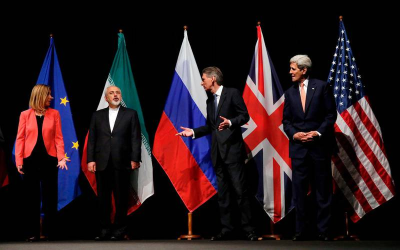 """(FILES) This file photo taken on July 14, 2015 shows then British Foreign Secretary Philip Hammond (2nd R), then US Secretary of State John Kerry (R) and European Union High Representative for Foreign Affairs and Security Policy Federica Mogherini (L) talking to Iranian Foreign Minister Mohammad Javad Zarif as they wait for the Russian Foreign Minister for a group picture at the Vienna International Center in Vienna, Austria, after reaching a nuclear deal. Israel welcomes a German push to expand the Iran nuclear deal into a broader security agreement once Joe Biden moves into the White House next month, its ambassador to Berlin told AFP. Jeremy Issacharoff, the nation's envoy in Germany since 2017, said a recent call by German Foreign Minister Heiko Maas to reassess the 2015 nuclear accord with a new US administration was a """"step in the right direction"""". / AFP / POOL / CARLOS BARRIA / TO GO WITH AFP INTERVIEW by DEBORAH COLE on December 24, 2020"""