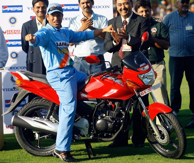 Indian cricketer Sachin Tendulkar gestures while posing with his Man of the Series prize - a motorbike - during the prize-giving ceremony after the fourth One Day International (ODI) match against the West Indies in Vadodara, 31 January 2007.  India won the four match ODI series by 3-1.  AFP PHOTO/ Indranil MUKHERJEE (Photo by INDRANIL MUKHERJEE / AFP)