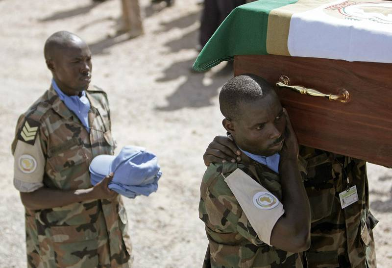 In a photograph made available by Albany Associates on July 12 2008, soldiers and civilian staff serving with the United Nations-African Union Mission in Darfur (UNAMID) pay their respects during a funeral ceremony for seven peacekeepers who were killed in an ambush by armed gunmen while returning from patrol in the Northern Darfur State on July 08. The deaths of the five Rwandan protection force peacekeepers and two police officers from Ghana and Uganda was the greatest loss of lives the mission has suffered since it took over from its African Union predecessor on 1 January this year. Twenty two others were wounded in the attack. STUART PRICE / ALBANY ASSOCIATES -RESTRICTED TO EDITORIAL USE- (Photo by STUART PRICE / ALBANY ASSOCIATES / AFP)