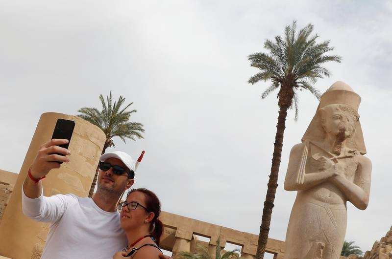 Tourists take a selfie picture with a mobile phone during their visit to Karnak Temple, following an outbreak of the coronavirus, in Luxor, Egypt March 9, 2020. REUTERS/Mohamed Abd El Ghany