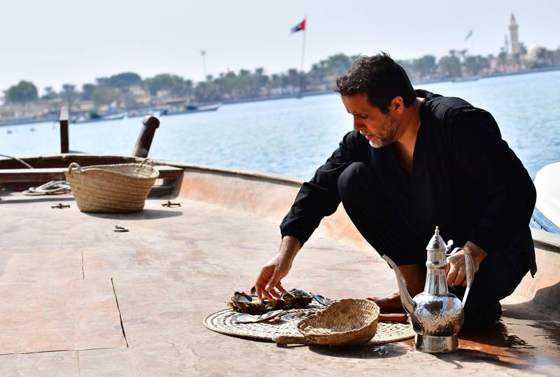 Emirati Abdullah al-Suwaidi open oysters to look for pearls at the Suwaidi's pearl farm, off the coast of al-Rams in the northern emirate of Ras al-Khaimah, on October 31, 2019. Suwaidi's project, one of a handful of operations in the United Arab Emirates, comes against a backdrop of increasing awareness of cultural traditions, such as falconry and camel racing, and efforts to promote and preserve them. Last month, Abu Dhabi authorities announced that the world's oldest natural pearl, found just off the capital at Marawah Island, would be displayed for the first time at the Louvre Abu Dhabi, the local outpost of the famous Paris museum.  / AFP / GIUSEPPE CACACE