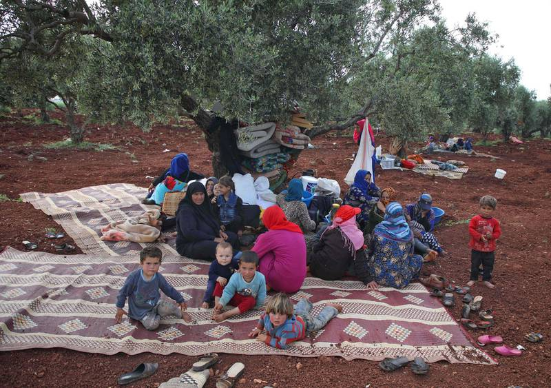 TOPSHOT - Displaced Syrians gather under the shade of a tree in a field near a camp for displaced people in the village of Atme, in the jihadist-held northern Idlib province on May 1, 2019. Bombardment by the regime and its Russian ally on northwestern Syria has displaced nearly 140,000 people since February, the UN said today.  / AFP / Aaref WATAD