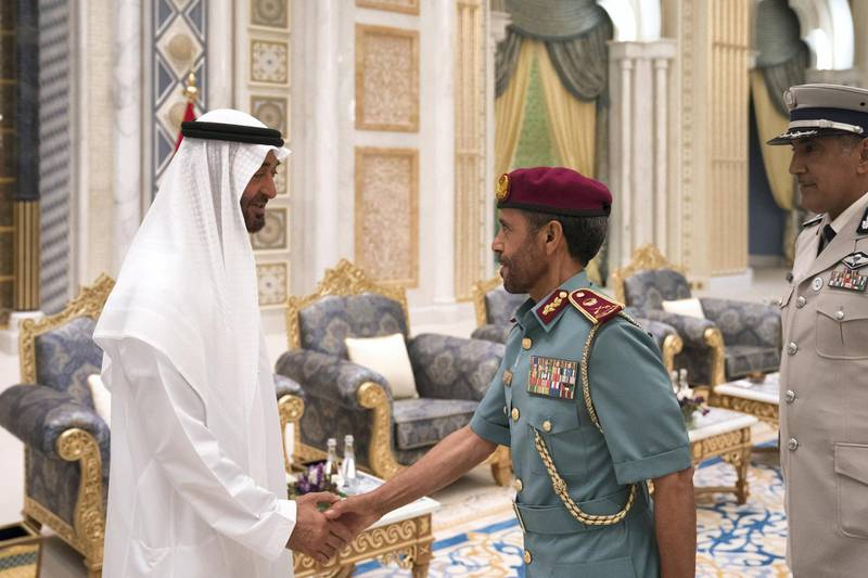 ABU DHABI, UNITED ARAB EMIRATES - May 20, 2018: HH Sheikh Mohamed bin Zayed Al Nahyan Crown Prince of Abu Dhabi Deputy Supreme Commander of the UAE Armed Forces (L), receives a member of the Abu Dhabi Police (C), during an iftar reception at the Presidential Palace. Seen with HE Major General Mohamed Khalfan Al Romaithi, Commander in Chief of Abu Dhabi Police and Head of Security, Justice, Health and Safety Committee of Abu Dhabi Executive Council (R).  ( Hamad Al Kaabi / Crown Prince Court - Abu Dhabi ) ---