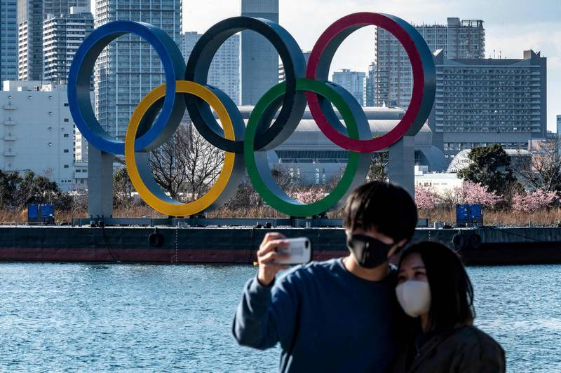 A couple pose for photos in front of the Olympic rings on display at the Odaiba waterfront in Tokyo on February 24, 2021. / AFP / Philip FONG
