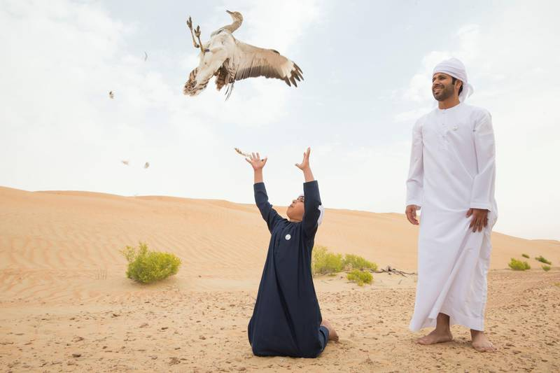 AL AIN, UNITED ARAB EMIRATES - Ali Al Shamsi from IFHC with his son Salem at the release of 50 Houbara birds into their Habitat of the UAE desert by The International Fund for Houbara Conservation (IFHC).  Leslie Pableo for The National