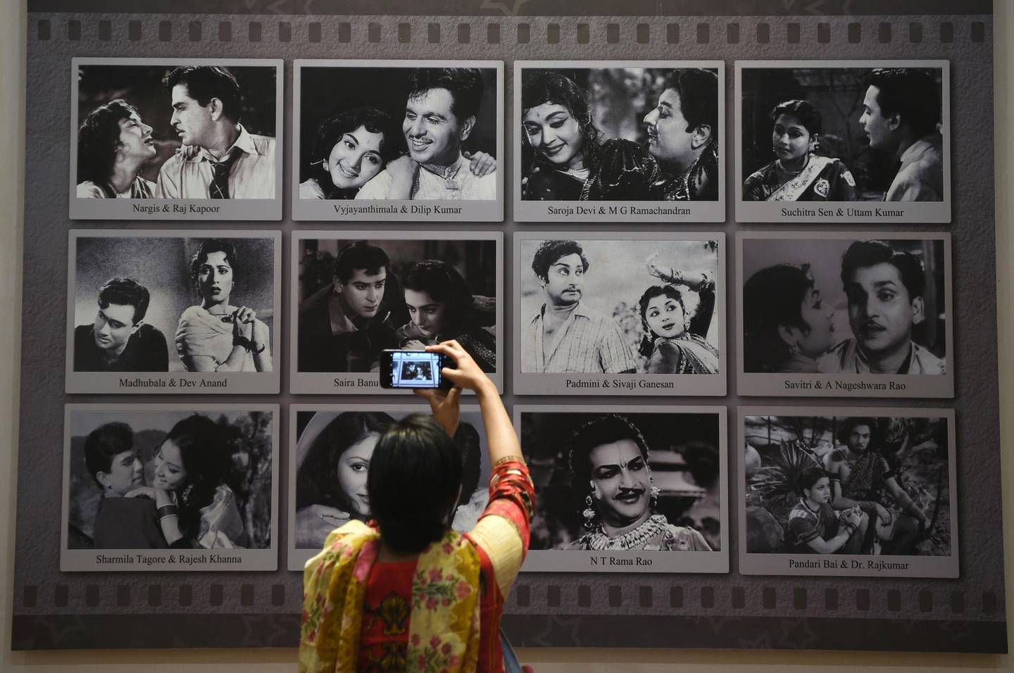 In this picture taken on January 22, 2019, a visitor takes a picture of a display with images of former Indian movie actors at the National Museum of Indian Cinema (NMIC), the country's first museum showcasing the history of its film industry, in Mumbai. From silent black-and-white films to colourful blockbusters bursting with song and dance, a new museum tracing the evolution of Indian cinema has opened in the home of Bollywood. Costing 1.4 billion rupees (19.6 million USD), India's first national film museum is spread across a stylish 19th-century bungalow and a modern five-storey glass structure in south Mumbai.  - TO GO WITH AFP STORY INDIA-ENTERTAINMENT-FILM-BOLLYWOOD-HISTORY-MUSEUM,FOCUS BY UDITA JHUNJHUNWALA AND PETER HUTCHISON  / AFP / PUNIT PARANJPE / TO GO WITH AFP STORY INDIA-ENTERTAINMENT-FILM-BOLLYWOOD-HISTORY-MUSEUM,FOCUS BY UDITA JHUNJHUNWALA AND PETER HUTCHISON