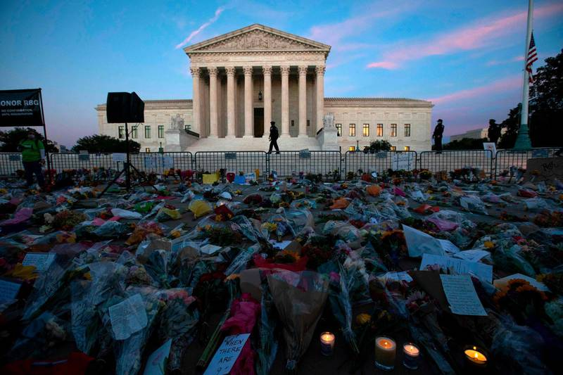 Flowers, candles, and signs are pictured at a makeshift memorial outside of the US Supreme Court as people pay their respects to Ruth Bader Ginsburg in Washington, DC on September 19, 2020. US President Donald Trump vowed to quickly nominate a successor, likely a woman, to replace late Supreme Court Justice Ruth Bader Ginsburg, only a day after the death of the liberal stalwart. / AFP / Jose Luis Magana