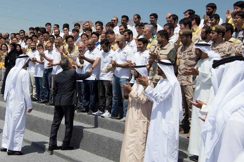 AL DHAFRA, ABU DHABI, UNITED ARAB EMIRATES - March 26, 2018: HE Moon Jea-In, President of South Korea (2nd L), greets an Emirates Nuclear Energy Corporation employee during the Unit One Construction Completion Celebration at Barakah Nuclear Energy Plant. Seen with HH Sheikh Mohamed bin Zayed Al Nahyan, Crown Prince of Abu Dhabi and Deputy Supreme Commander of the UAE Armed Forces (L), HH Sheikh Tahnoon bin Mohamed Al Nahyan, Ruler's Representative in Al Ain Region (3rd L) and HH Sheikh Nahyan Bin Zayed Al Nahyan, Chairman of the Board of Trustees of Zayed bin Sultan Al Nahyan Charitable and Humanitarian Foundation (4th L).     ( Abdullah Al Junaibi ) ---