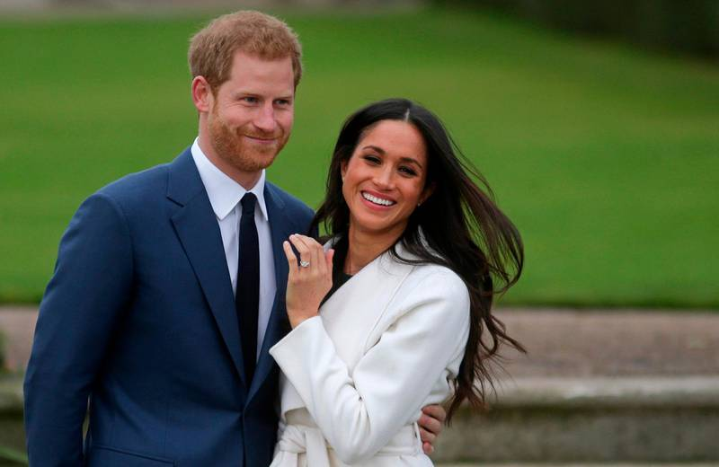 (FILES) In this file photo Britain's Prince Harry stands with his fiancée US actress Meghan Markle as she shows off her engagement ring whilst they pose for a photograph in the Sunken Garden at Kensington Palace in west London on November 27, 2017, following the announcement of their engagement. Queen Elizabeth II and other senior British royals were gathering for a meeting Monday with Prince Harry in an attempt to solve the crisis triggered by his bombshell announcement that he and wife Meghan were stepping back from the royal frontline. Harry's father Prince Charles and brother Prince William, with whom he has strained relations, will join the monarch at her private Sandringham estate in eastern England, according to British media. / AFP / Daniel LEAL-OLIVAS