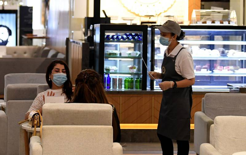 Women wearing masks for protection against the coronavirus, sit at a restaurant in the Mall of Dubai on April 28, 2020, after the shopping centre was reopened as part of moves in the Gulf emirate to ease lockdown restrictions imposed last month to prevent the spread of the COVID-19 illness.  / AFP / Karim SAHIB