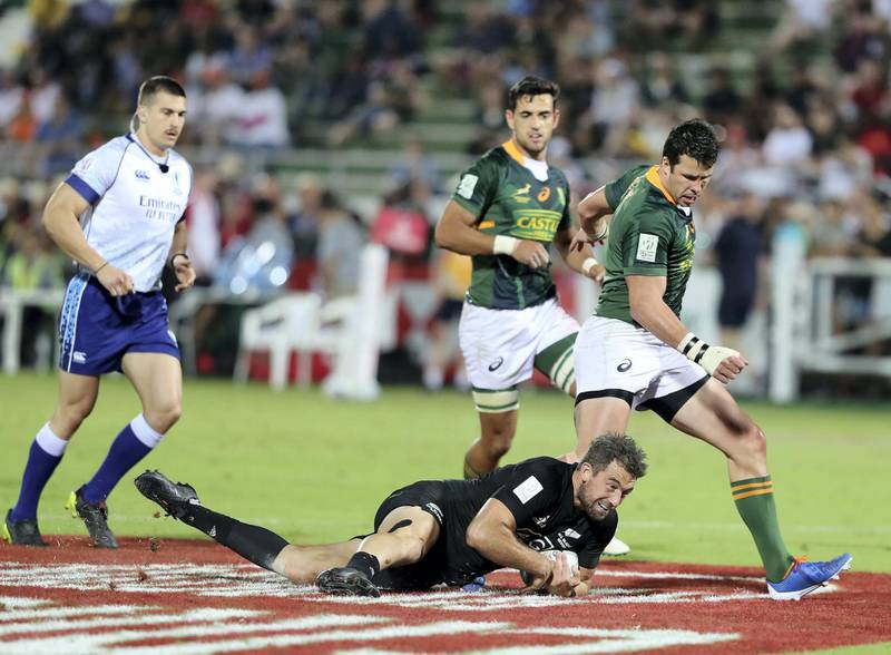 Dubai, United Arab Emirates - December 07, 2019: Kurt Baker of New Zealand gathers the ball over Ruhan Nel of South Africa during the game between New Zealand and South Africa in the mens final at the HSBC rugby sevens series 2020. Saturday, December 7th, 2019. The Sevens, Dubai. Chris Whiteoak / The National
