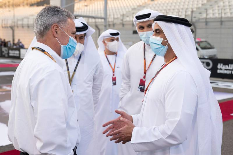 YAS MARINA, ABU DHABI, UNITED ARAB EMIRATES - December 13, 2020: HH Lt General Sheikh Saif bin Zayed Al Nahyan, UAE Deputy Prime Minister and Minister of Interior (R), speaks with Chase Carey, Formula 1 Chairman and CEO (L), during on the pit lane prior to the final race of the 2020 Formula 1 Etihad Airways Abu Dhabi Grand Prix, at Yas Marina Circuit.   ( Hamad Al Kaabi / Ministry of Presidential Affairs ) ---