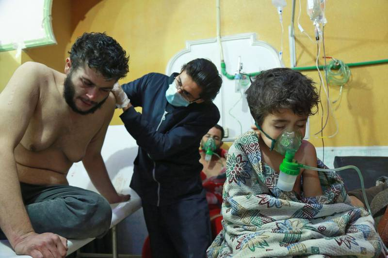 Syrian children and adults receive treatment for a suspected chemical attack at a makeshift clinic on the rebel-held village of al-Shifuniyah in the Eastern Ghouta region on the outskirts of the capital Damascus late on February 25, 2018.   A child died and at least 13 other people suffered breathing difficulties after a suspected chemical attack on the besieged Syrian rebel enclave, a medic and a monitor said. The Britain-based Syrian Observatory for Human Rights said 14 civilians had suffered breathing difficulties after a regime warplane struck the village.   / AFP PHOTO / HAMZA AL-AJWEH