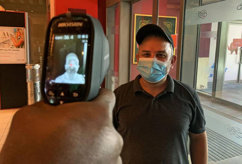 A man, wearing protective masks to prevent the spread of the coronavirus, has his temperature taken at the Ibn Battuta mall in the Emirate of Dubai on April 27, 2020. The United Arab Emirates decided on April 23 to reopen malls, cafes and restaurants and ease lockdown restrictions imposed last month to prevent the spread of coronavirus on the occasion of Ramadan. / AFP / GIUSEPPE CACACE