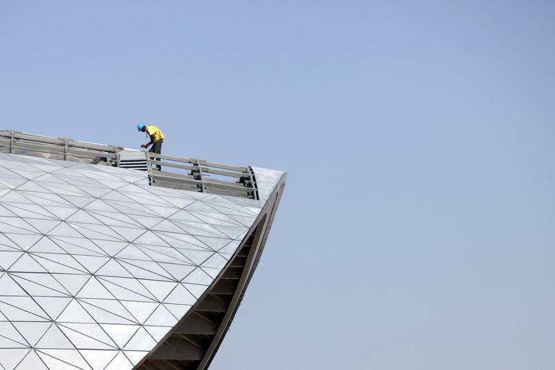 Abu Dhabi, UAE - March 15, 2010 - A laborer works on the roof of the library of the Masdar Institute of Science and Technology at Masdar City. The city plans to rely entirely on solar energy and other renewable energy sources, with a sustainable, zero-carbon, zero-waste ecology. (Nicole Hill / The National