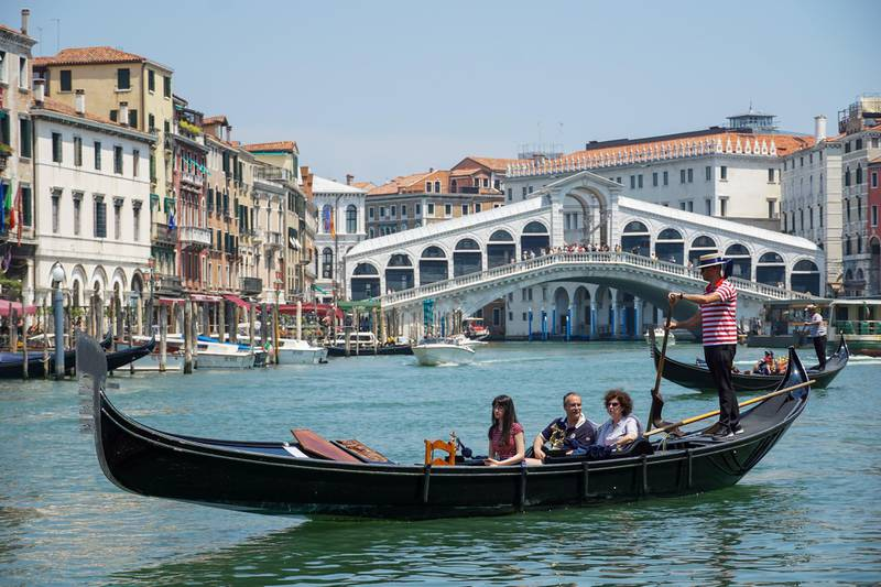 Tourists ride a gondolier in view of the Rialto Bridge on the Grand Canal in Venice, Italy, on Saturday, June 13, 2020. The shuttering of businesses led to a 5.3% decline ingross domestic productin the first quarter, and a far deeper slump is anticipated this quarter. Photographer: Andrea Merola/Bloomberg