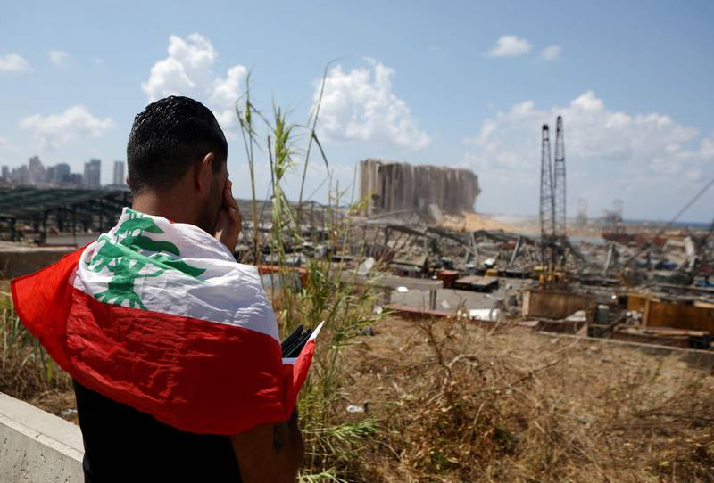 TOPSHOT - A man draped in a Lebanese flag reacts as he stands before the ravaged port of Lebanon's capital Beirut on August 9, 2020, in the aftermath of a colossal explosion that occurred days prior due to a huge pile of ammonium nitrate that had languished for years at a port warehouse. The huge chemical explosion that hit Beirut's port, devastating large parts of the Lebanese capital and claiming over 150 lives, left a 43-metre (141 foot) deep crater, a security official said. The blast Tuesday, which was felt across the country and as far as the island of Cyprus, was recorded by the sensors of the American Institute of Geophysics (USGS) as having the power of a magnitude 3.3 earthquake. / AFP / PATRICK BAZ
